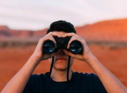 Man looking through binoculars in desert