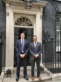 Dr Sachin Sende and Giles Barker in front of door at number 10 Downing Street, London